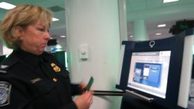 CBP Area Port Director Patty Fitzpatrick shows off how to use a kiosk at Charlotte Douglas International Airport on Tuesday.