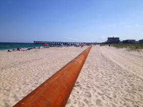 A dredging pipe extends down Wrightsville Beach.