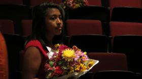Circle de Luz graduate Mayra holds a bouquet of flowers after the ceremony on June 19.