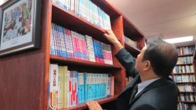Ki-Hyun Chun reaches for a book in the Chinese children's book section at the Asian Library.