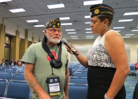 Verna Jones, staff director at the American Legion office in Washington, D.C. holds the microphone for John Worholak of South Carolina.