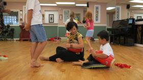 XiaoSong He shows a student how to play the Chinese waist drum during a summer program at the Asian Library.