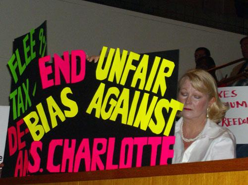 Some residents of south Charlotte held signs expressing their oppisition of proposed tax increase. Photo: Julie Rose