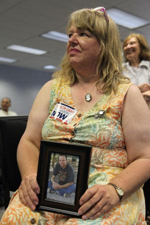 Leslie Boyd of Asheville carries a picture of her son Mike Danforth. She says Danforth could not obtain health insurance because