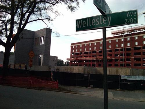 The new red brick parking garage topped with two floors of student housing sits beyond the athletic center seen in the
