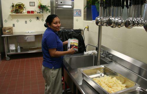 A cafeteria staff member making an apple crisp dessert for tomorrow's lunch.