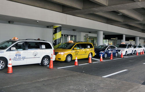 New taxis await customers at the airport baggage claim exit.
