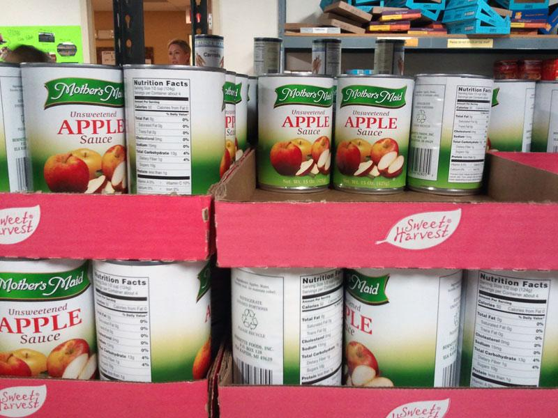 Cans of applesauce at a Loaves and Fishes food pantry in Uptown Charlotte.