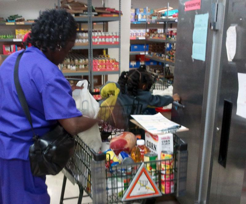 Cynthia Jackson gets food for her family from a Loaves and Fishes food pantry.