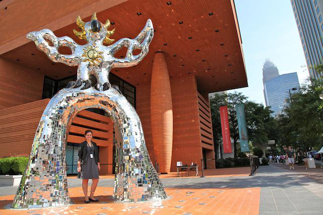 Cathie Burns, the collections management assistant at the Bechtler Museum of Modern Art, stands with the Firebird.
