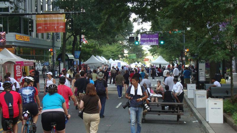 Vendors, DNC volunteers and local visitors walk through displays at CarolinaFest as it opened around 10 AM Monday.
