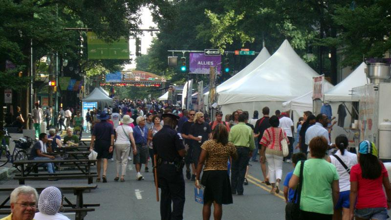 Early CarolinaFest visitors near the main stage at Trade and Tryon Streets late on Monday morning.
