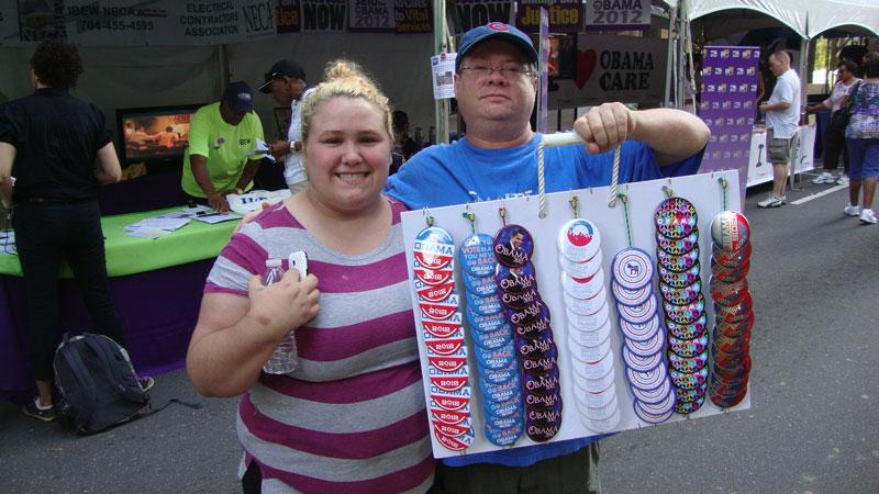 Charlotte street  vendors who identify themselves as Danny and Colleen sell logo pins to DNC faithful at CarolinaFest on Monday.