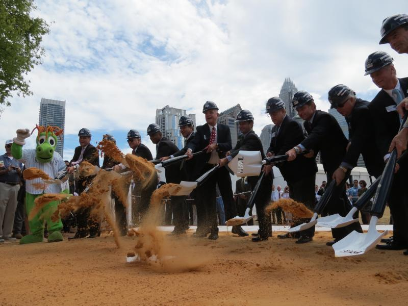 Charlotte Knights owners, supporters use ceremonial shovels to toss sand on home plate of the new baseball stadium to be completed uptown in 2014.
