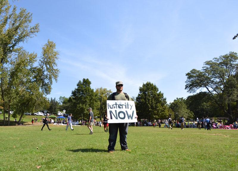 A protester advertises his hope for financial sustainability in the next administration before the march of about 800 left from Frazier Park on Sunday.
