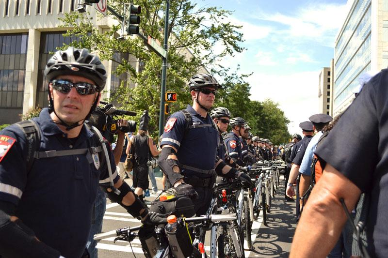 Police officers with bicycles close off Tryon Street from March on Wall Street South protesters as they follow Stonewall Street.