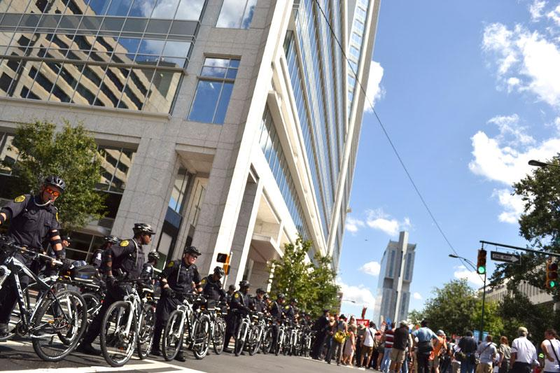 Outside the Duke Energy Building, a row of police officers stand watch and one takes a sip of water. Temperatures reached 92 degrees and protesters were lead to a water fountain to fill up their bottles along the route.