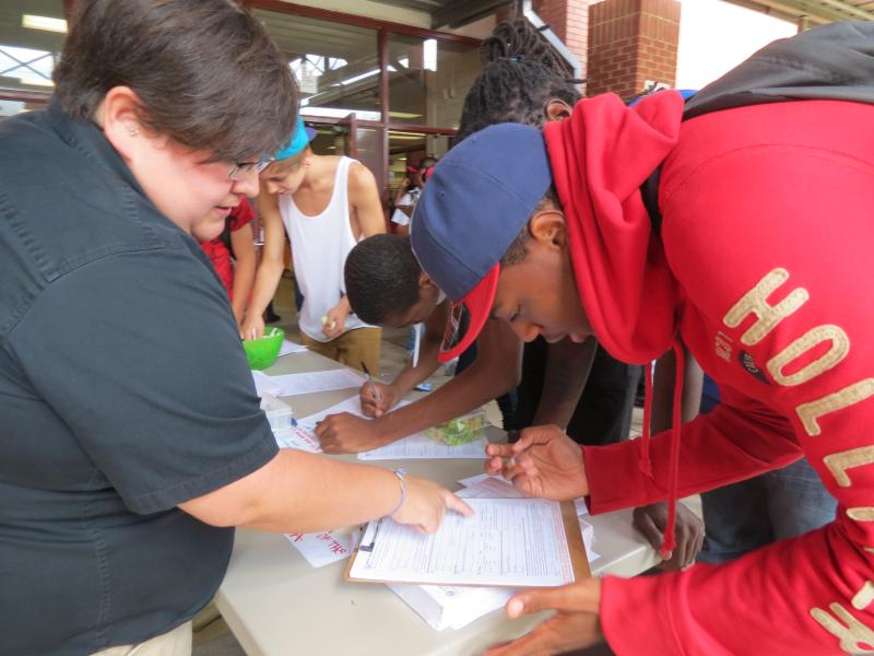 Lacey Williams of the Latin American Coalition helps a student at West Mecklenburg High School fill out a voter registration form.
