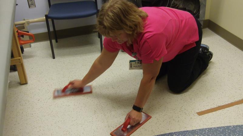 Physical therapist Sandie Warantz demonstrates sweeping the floor with rubber floats (used to smooth out concrete) to show what potential applicants to a local construction company are asked to do as part of their fitness exam.