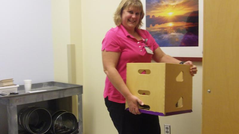 Physical therapist Sandie Warantz lifts a box full of weights to show what potential applicants to a local construction company had to lift.