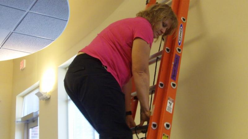 Physical therapist Sandie Warantz climbs an extension ladder to show what potential applicants to a local construction company are asked to do as part of their fitness exam.