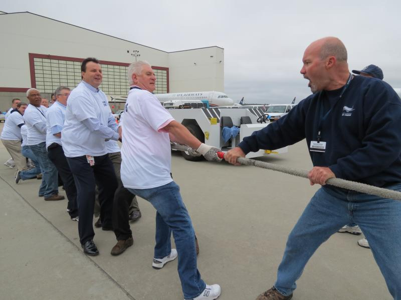 Captain Ed Bular leads his team at the event (and in real life). He is US Airways' senior vice president. Cary Braden, a US Airways corporate trainer, yells at the team to pull.