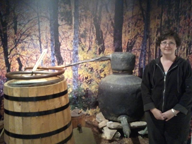Wilkes Heritage Museum Director Jennifer Furr stands in front of a moonshine still on display there