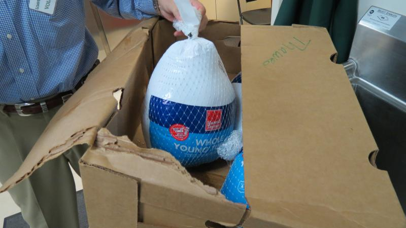 A volunteer at the uptown Loaves and Fishes food pantry takes turkeys out of a box to give to families.