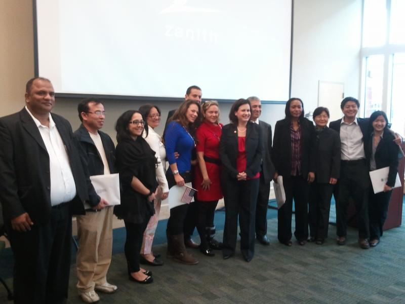 Twelve new U.S. citizens and N.C. Rep. Tricia Cotham stand together after a naturalization ceremony.