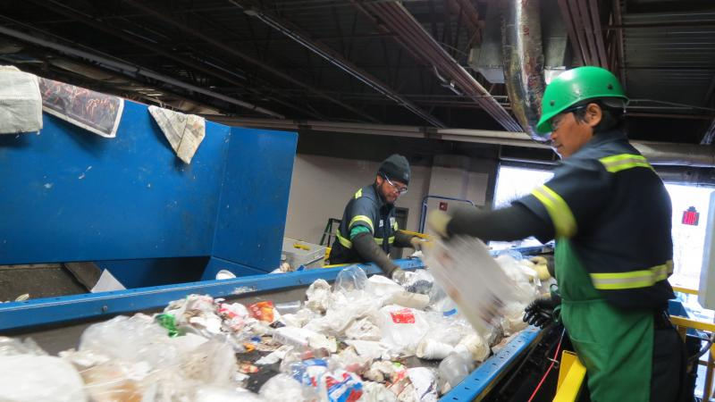 Workers at the Charlotte Airport Recycling Center pull recyclable material off a conveyor belt as 25 tons of trash passes through each day.