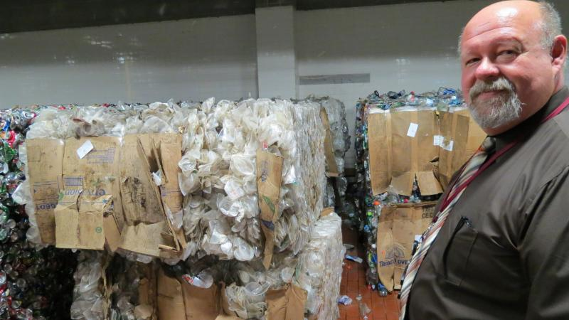 Charlotte Airport Housekeeping Manager Bob Lucas with bales of plastic cups.