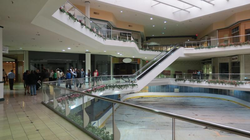 People interested in buying or developing Eastland Mall look over a railing at the old ice rink.