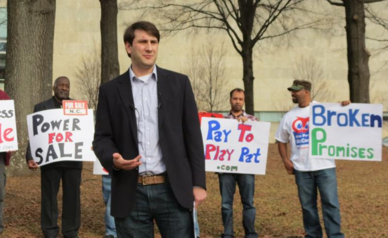 Justin Guillory of Progress North Carolina stands in front of people holding protest signs against Gov. Pat McCrory.