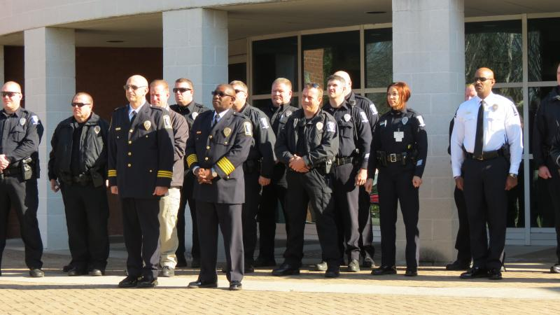 Officers at the Freedom Division watch as the flag is added outside their division.