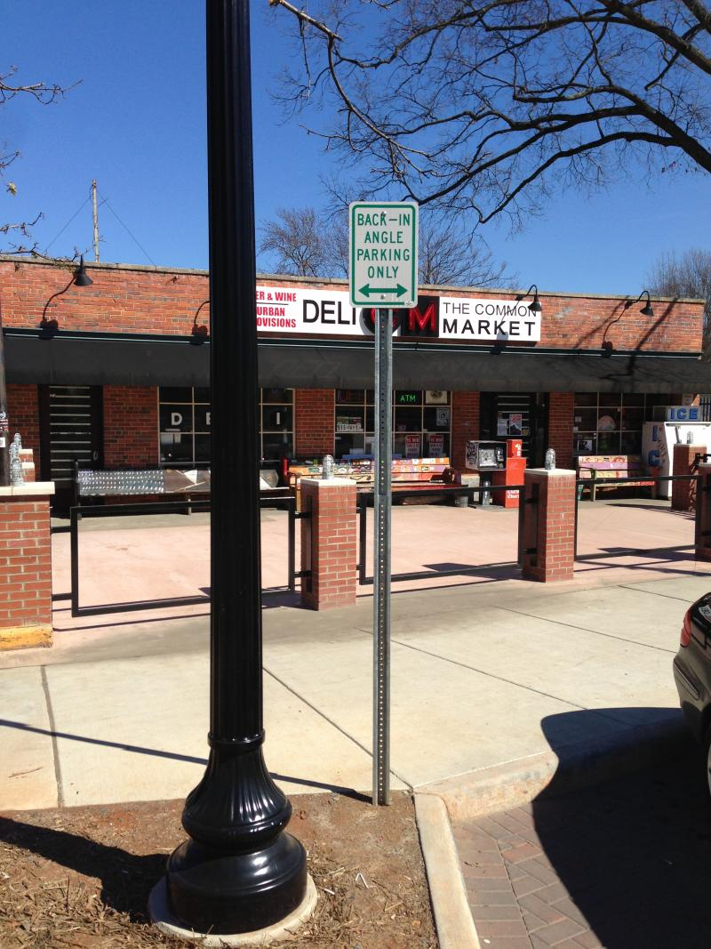 """More signs marking the spaces as """"back-in angle parking only""""."""