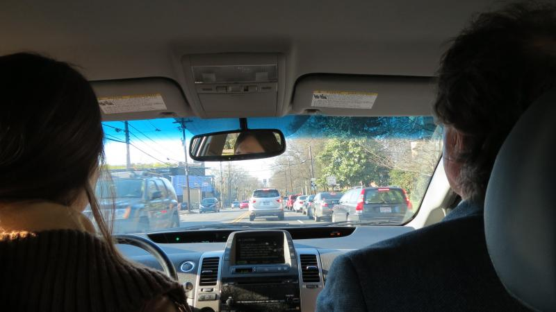 WFAE reporter Lisa Miller and UNC Charlotte professor Martin Kane wait at a red light on Providence Road.