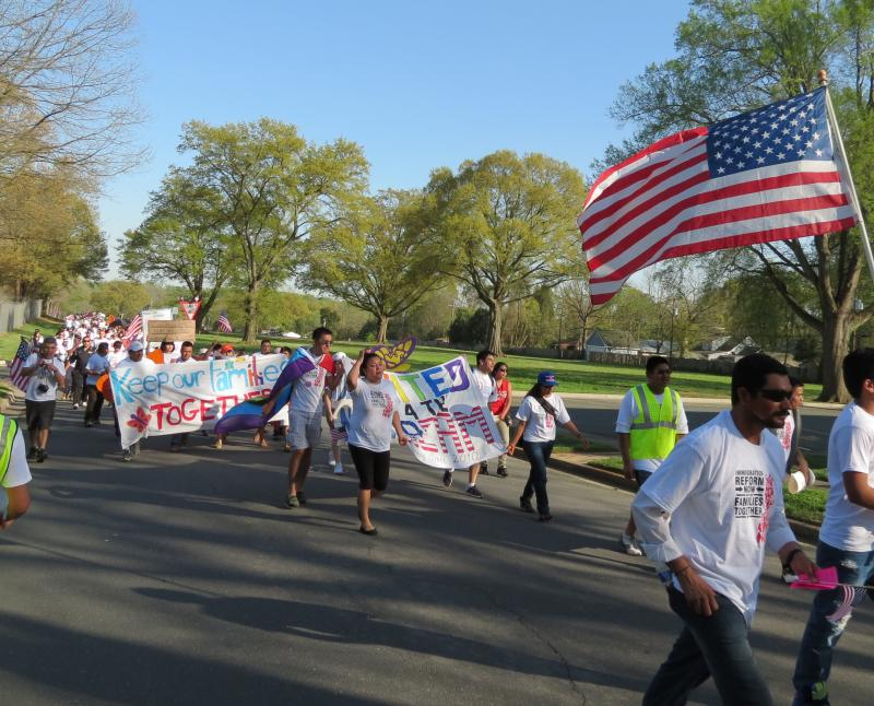 People carry flags and signs at the front of the march.