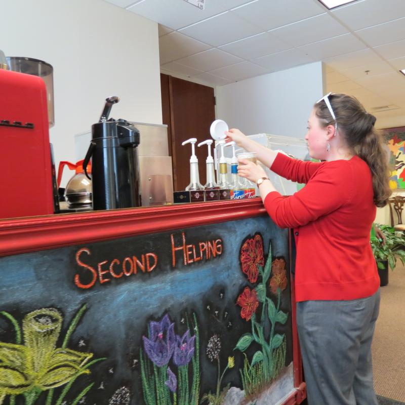 Mariclaire Hicks, an intern with Safe Alliance, grabs coffee from the Second Helping coffee cart in uptown Charlotte.