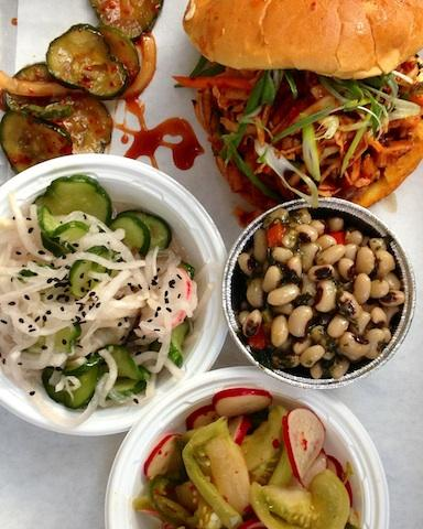 Spicy Korean pork sandwich, black eyed pea salad, green tomato kimchi, and cucumber and radish salad  at Heirloom Market BBQ, Atlanta.