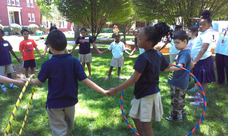 Students play a game with hula hoops at Queens University