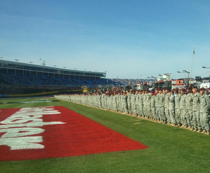 Troops line the infield of the Charlotte Motor Speedway as part of the Memorial Day celebration for the Coca-Cola 600. The FOX overhanging camera system stretches across the speedway on the left.