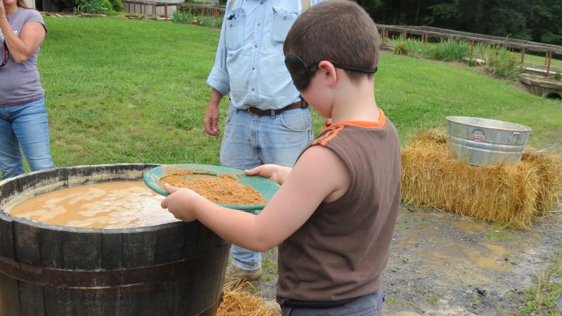 Ben Buffington, 6, pans for gold blind-folded as part of the panning competition. He won third place in the kid category.