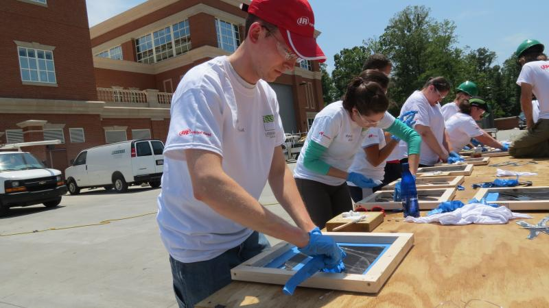 Alex Miller of Ingersoll Rand prepares to pour fly-ash concrete over his tile template.