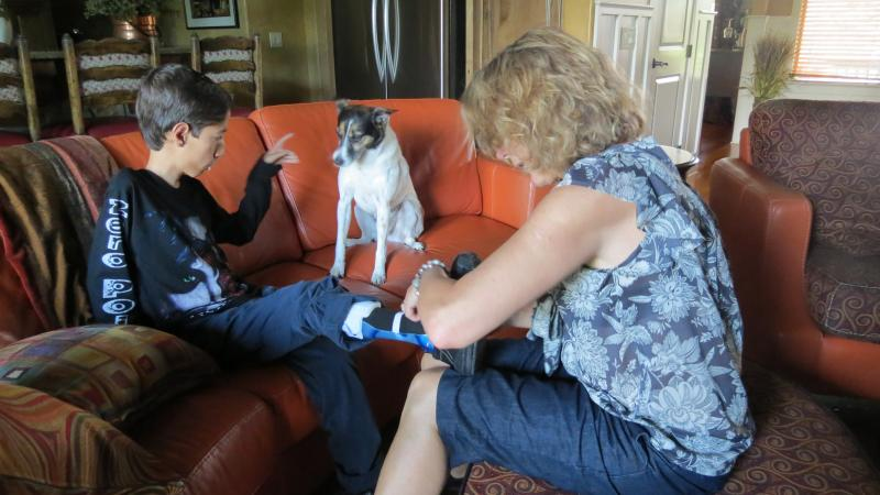 Menhaj instructs the family dog to sit while Cindy takes off Menhaj's braces before they go to the pool.