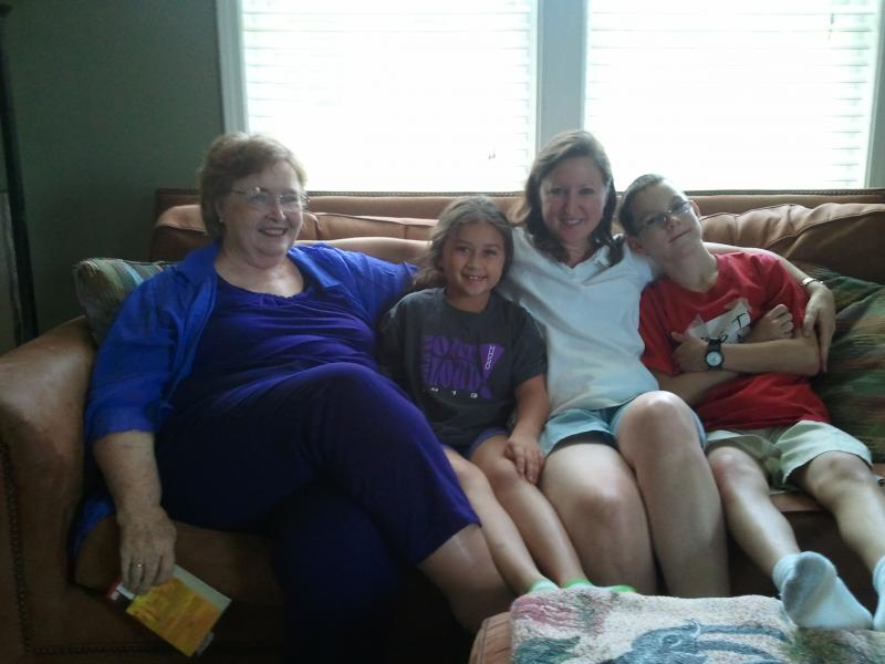 Sharla Bond sits in a white shirt with her son Greyson, her niece and her mother.