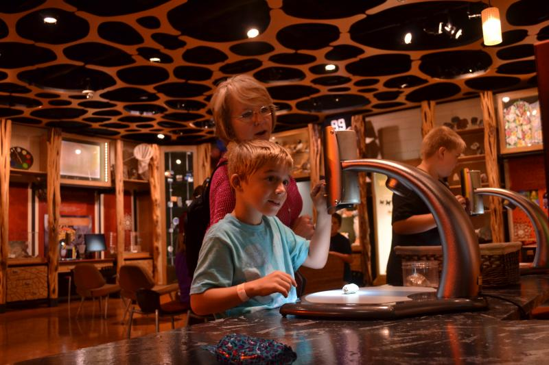 A boy looks through a microscope at Discovery Place, a major recipent of ASC funds.