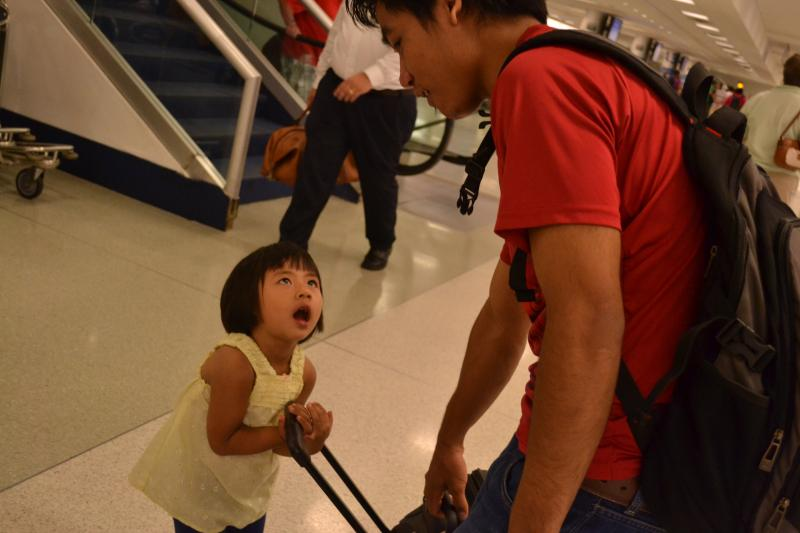 Many refugee families choose to be resettled in the same city as close friends or family. Here, the great-neice of a recent refugee arrival tries to help with the luggage.