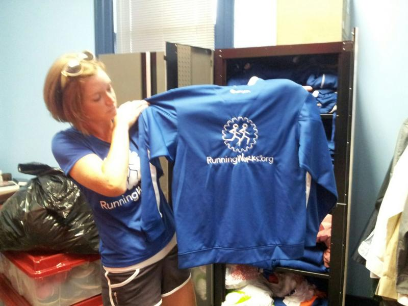RunningWorks Director Meredith Dolhare shows off a shirt that particpants wear.
