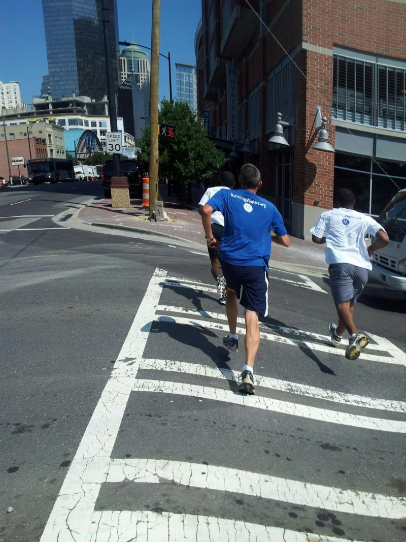 "Participants in the Urban Ministry Center's ""RunningWorks"" program run through Uptown Charlotte."
