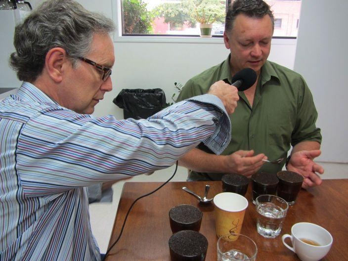 David Haddock demonstates the proper way to taste test coffee at Boquete Mountain Coffee Roasters while Mike records.